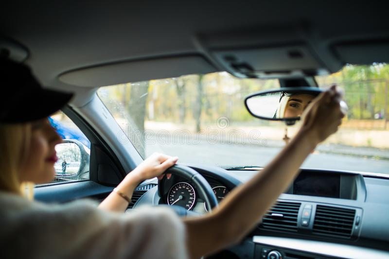 Der glückliche Fahrer der jungen Frau, der schaut, justierend den Autospiegel der hinteren Ansicht, der Linie vergewissernd, ist  stockfotos