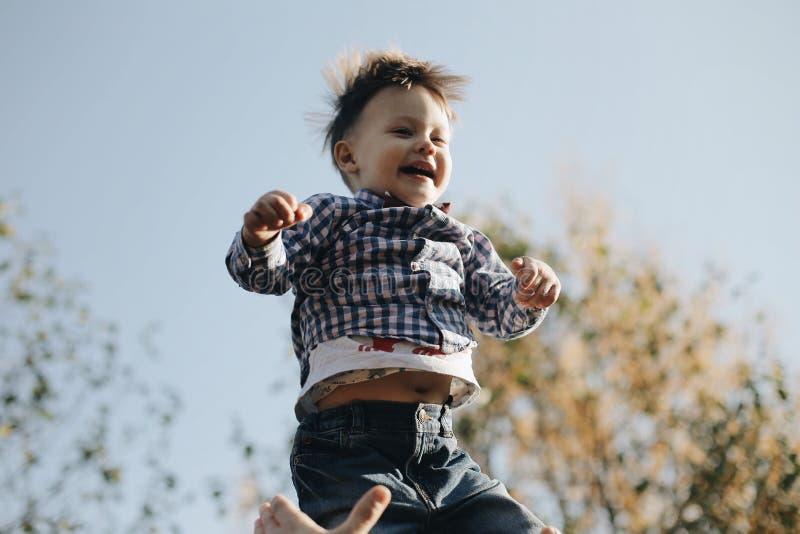 Der glückliche frohe Vater, der Spaß hat, wirft in der Luft Kind Sohn lacht stockfotografie