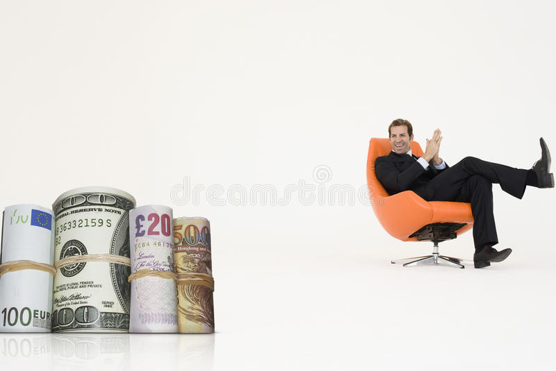 Der glückliche Geschäftsmann, der Geld betrachtet, rollt, Wachstum im internationalen Geschäft darstellend lizenzfreies stockfoto