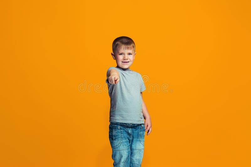 Der glückliche jugendlich Junge, der auf Sie, halbes Längennahaufnahmeporträt auf orange Hintergrund zeigt lizenzfreie stockfotos