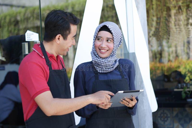 Der glückliche junge Paarcaféinhaber, der Tablet-Computer vor Glaseingang verwendet, beim Schauen jeder des anderen besprechen ih lizenzfreies stockfoto