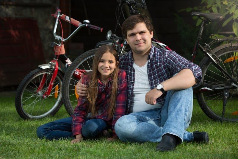 Der glückliche junge Vater, der mit Tochter auf Gras am Park sich entspannt, nach dem Reiten rad, fährt lizenzfreie stockfotos