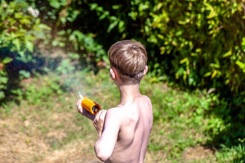 Der glückliche kleine Junge, der Spaß mit hat, spritzen Gewehr im Garten lizenzfreie stockbilder