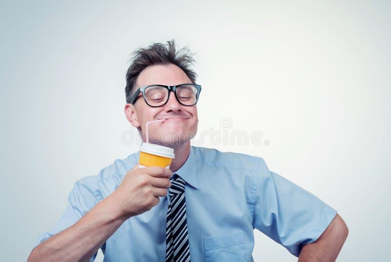Der glückliche Mann in den Gläsern trinkend von einer Papierschale mit einem Stroh, Augen schloss mit Vergnügen lizenzfreies stockbild