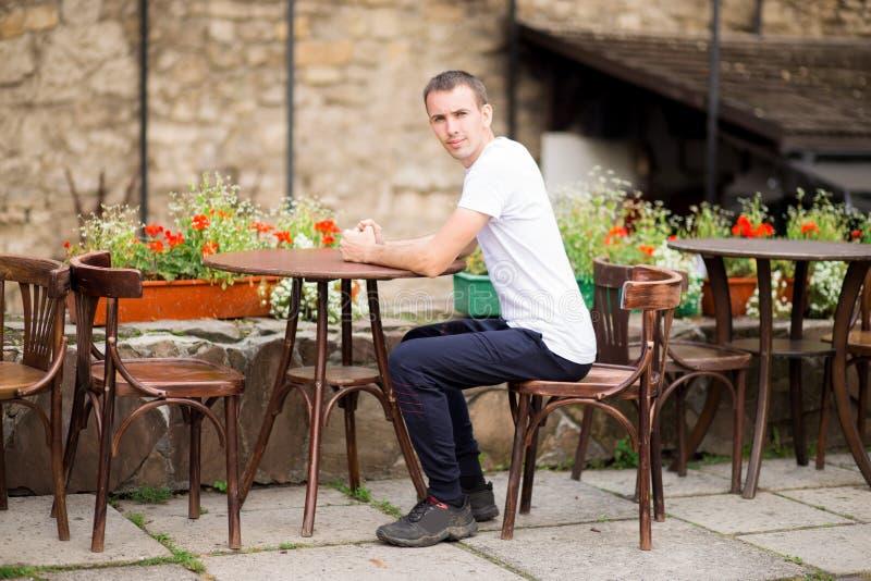 Der glückliche Mann, der Kaffeepause am Freiencafé in altem hat, europen Stadt stockfoto