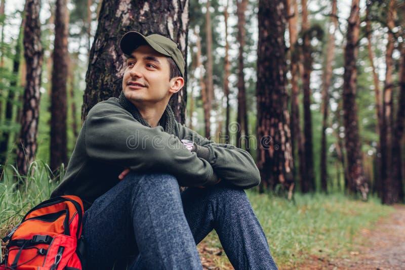 Der glückliche Manntourist, der im Frühjahr Waldreisenden stillsteht, stoppte, um sich zu entspannen Kampieren, Reisen und Sportk stockbilder