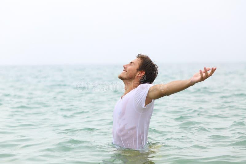 Der glückliche Mensch, der sich am Strand ausstreckt stockbild