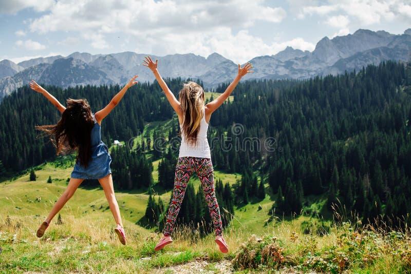 Der glückliche Sprung von zwei Mädchen in den Bergen unterstützen Ansicht stockfotografie