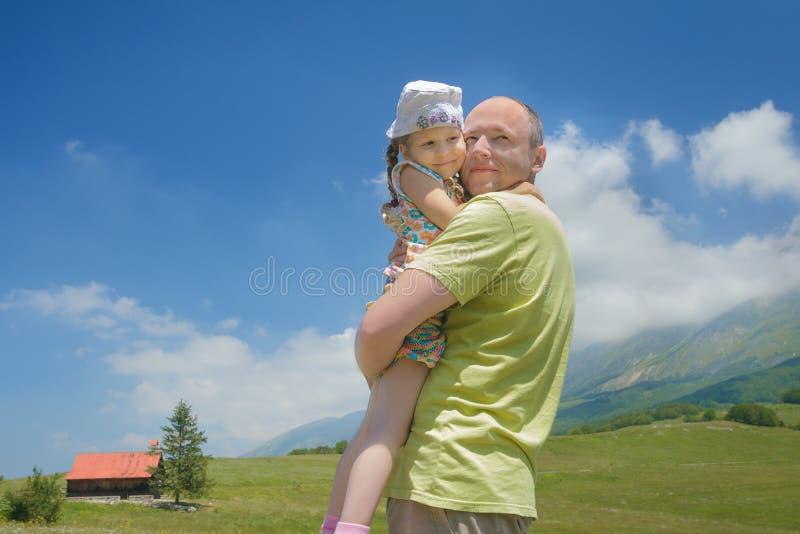 Der glückliche Vater, der kleine Tochter auf seinem hält, bewaffnet hohe Alpenwiese lizenzfreie stockbilder