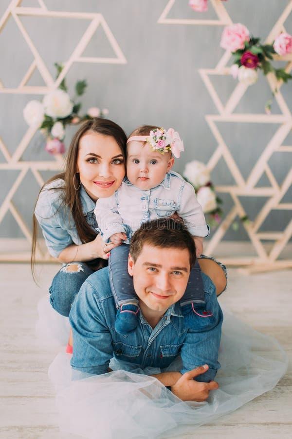 Der glückliche Vater mit dem Baby auf seinen Schultern liegt auf dem Tulle, während die Mutter das Baby umarmt lizenzfreies stockbild