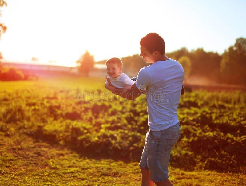 Der glückliche Vater- und Kindersohn, der Spaß zusammen, an halten hat, überreicht sonnigen Abendsonnenuntergang lizenzfreie stockfotos