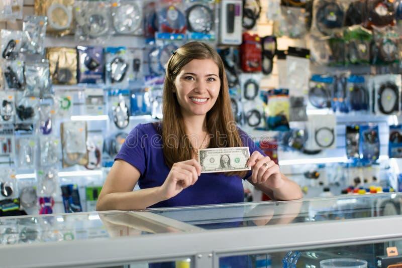 Der glückliche weibliche Computer-Ladenbesitzer, der ersten Dollar zeigt, erwerben stockfotos