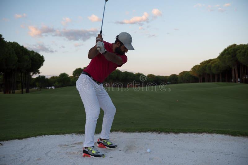 Der Golfspieler, der einen Sandbunker schlägt, schoss auf Sonnenuntergang stockfoto