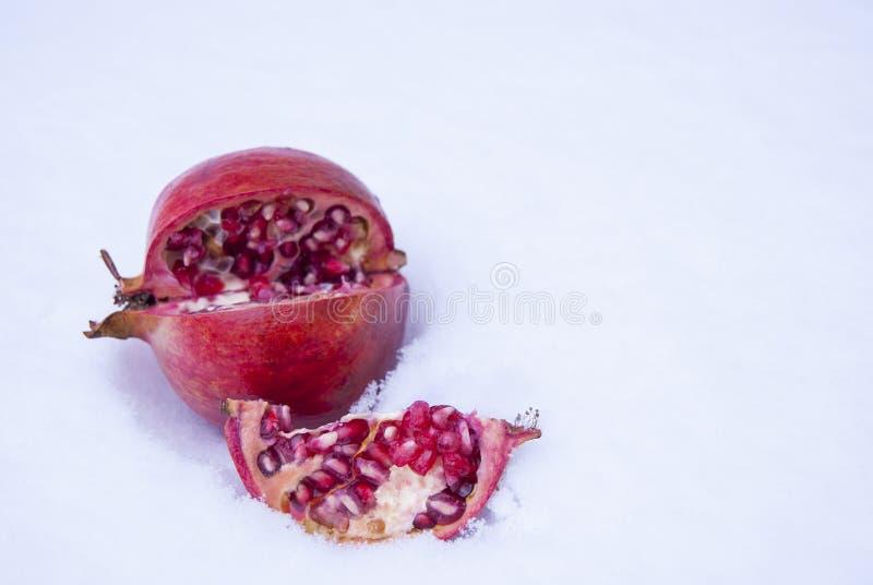 Der Granatapfel ist rot, reif und seitlich liegt auf dem Schnee lizenzfreies stockbild