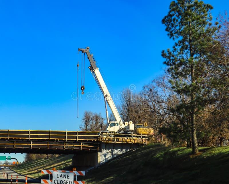 Der große weiße mobile Kran, der an Brücke über einer Landstraße mit Weg arbeitet, schloss durch hohe Kiefer lizenzfreie stockfotografie