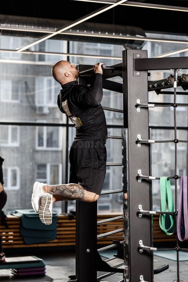 Der grobe athletische Mann, der in der schwarzen Artkleidung gekleidet wird, zieht auf der Stange in der Turnhalle hoch lizenzfreies stockbild