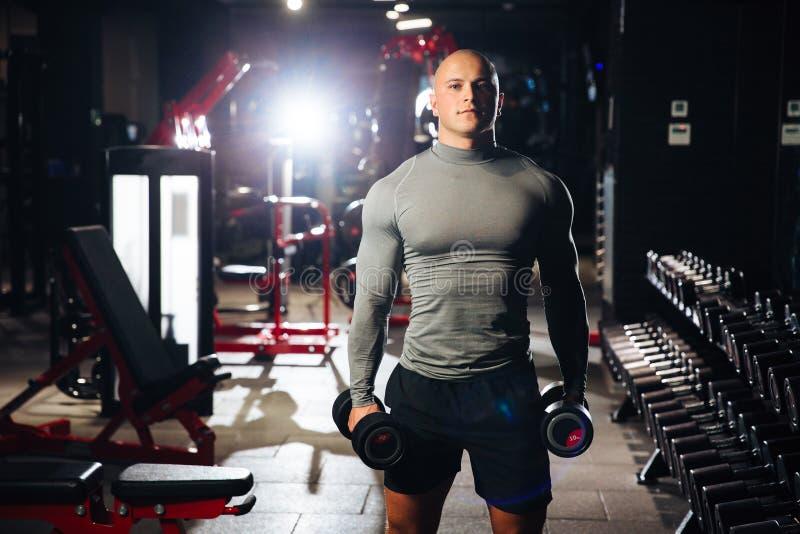 Der grobe muskulöse Mann, der Sport tut, trainiert mit Dummköpfen in der Turnhalle Ein starker Kerl nimmt an Eignung teil Konzept stockfotografie