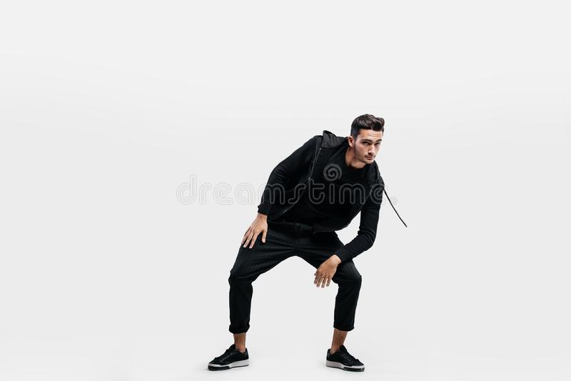 Der hübsche junge Mann, der in der Kleidung eines Sportschwarzen gekleidet wird, tanzt Straßentanz lizenzfreies stockfoto
