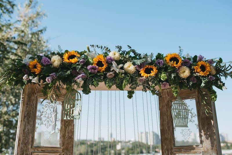 Der hölzerne Hochzeitsbogen in Provence-Art verziert mit Blumen, Sonnenblumen und anderem Sommer blüht stockfotografie