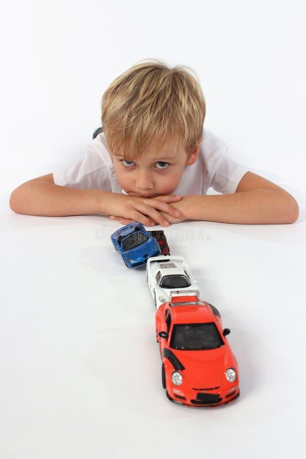 Der hübsche entzückende kleine Junge, der hinter einer Linie von Autospielwaren mit den Armen liegt, kreuzte und gebohrt, der sch lizenzfreie stockfotografie