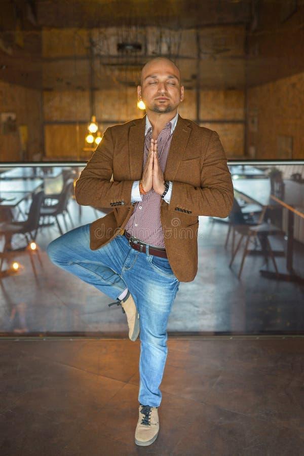 Der hübsche indische Geschäftsmann, der in der Klage durchführt Yoga oder asana, um sich zu entspannen weared ist, Augen schloss stockbilder