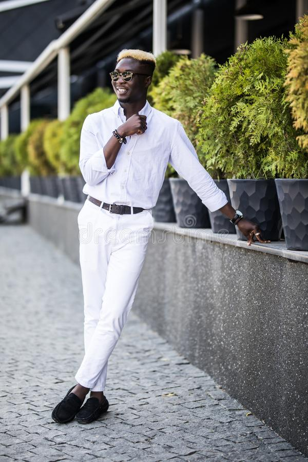 Der hübsche junge afroe-amerikanisch Geschäftsmann, der stilvolle Kleidung in der modernen Stadt trägt, sitzt nahe dem Gebäude lizenzfreies stockbild