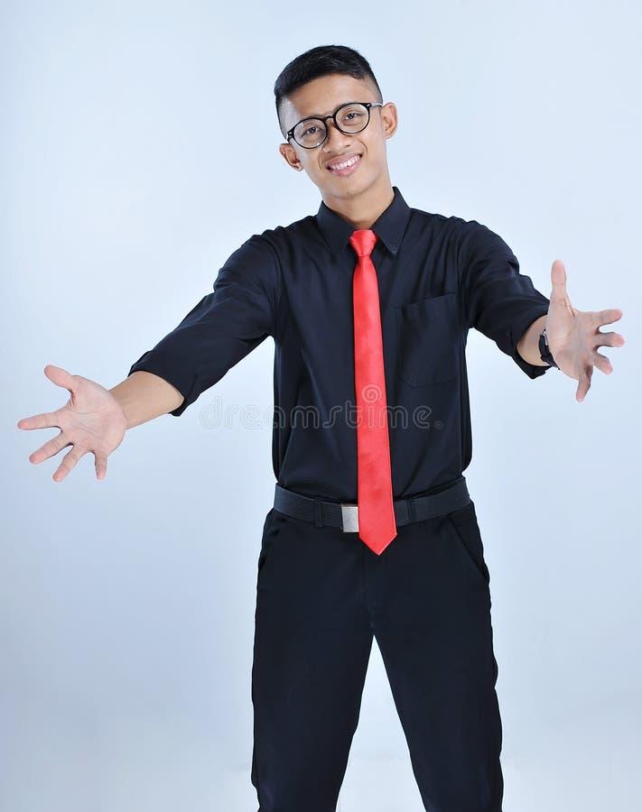 Der hübsche junge asiatische glückliche und lächelnde Geschäftsmann tun eine Umarmungsgeste mit Glas- und roter Bindung lizenzfreies stockfoto