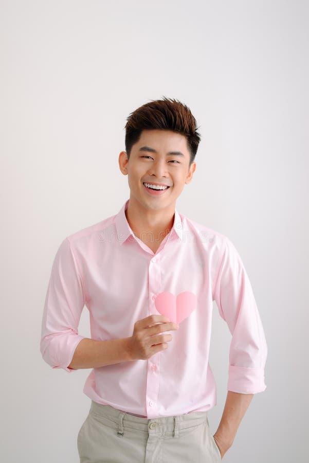 Der hübsche junge asiatische Mann, der Papierherz hält, formte Valentinsgruß lizenzfreie stockbilder