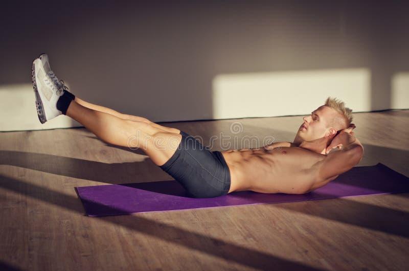 Der hübsche junge Mann, der ABS tut, trainiert auf Matte stockfoto