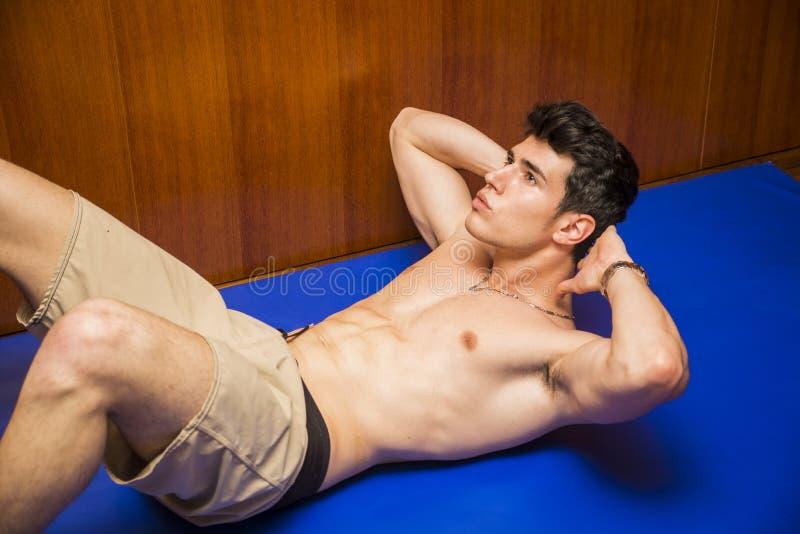 Der hübsche junge Mann, der ABS tut, trainiert auf Matte lizenzfreie stockbilder