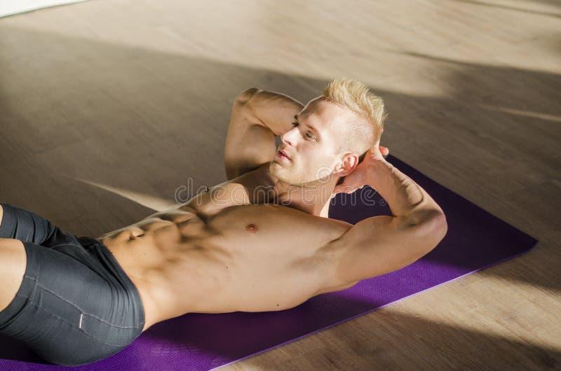 Der hübsche junge Mann, der ABS tut, trainiert auf Matte lizenzfreies stockfoto