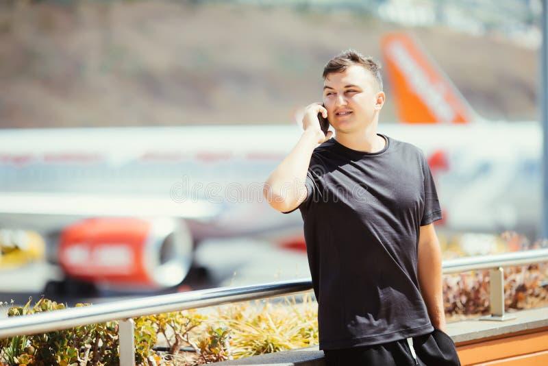 Der hübsche junge Mann, der am Telefon spricht, steht an der Terrasse im Flughafenabfertigungsgebäude beim Warten auf den Flug mi lizenzfreies stockbild