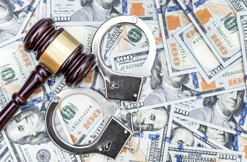 Der Hammer des Richters mit den Handschellen auf dem Hintergrund von Dollarscheinen lizenzfreie stockfotografie