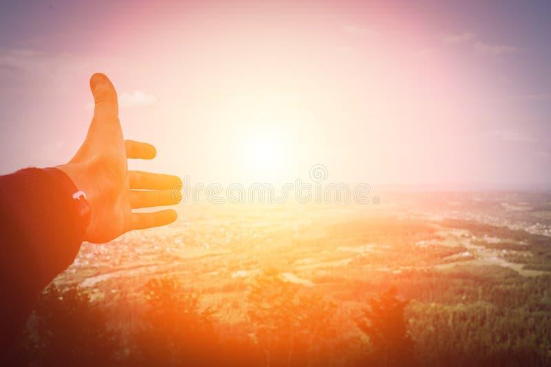 Der Handmann, der mit auf Sonnenuntergang im Berggebiet zeigt, entspannen sich Konzept und Reise lizenzfreie stockfotografie