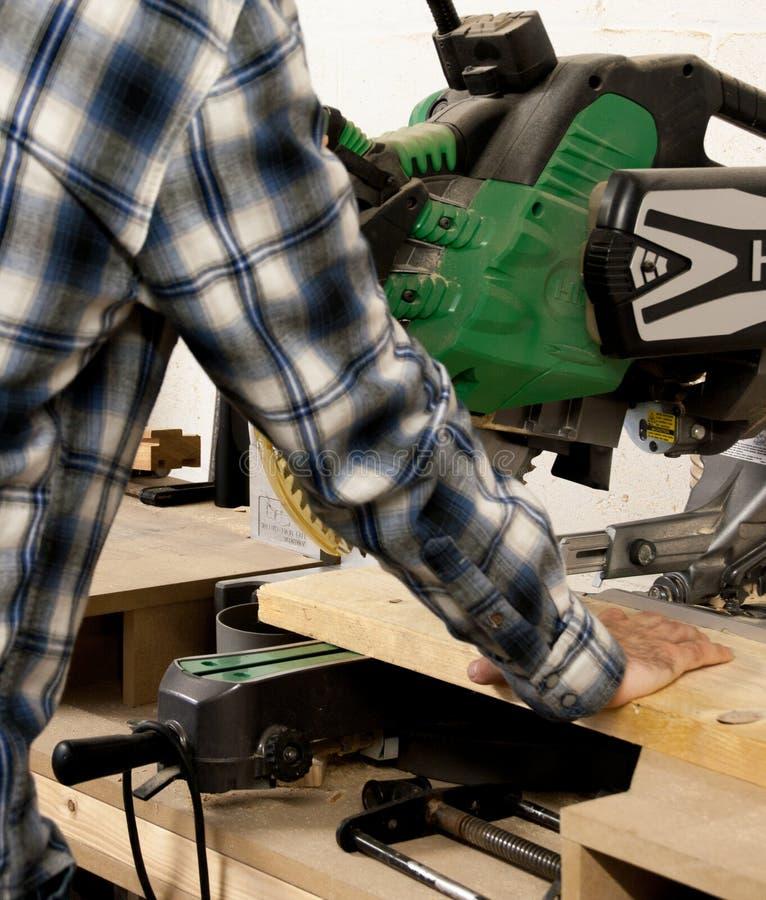 Der Handwerker, der die Gehrungsfuge verwendet, sah, um ein Stück Holz zu schneiden, um zu sortieren stockfoto