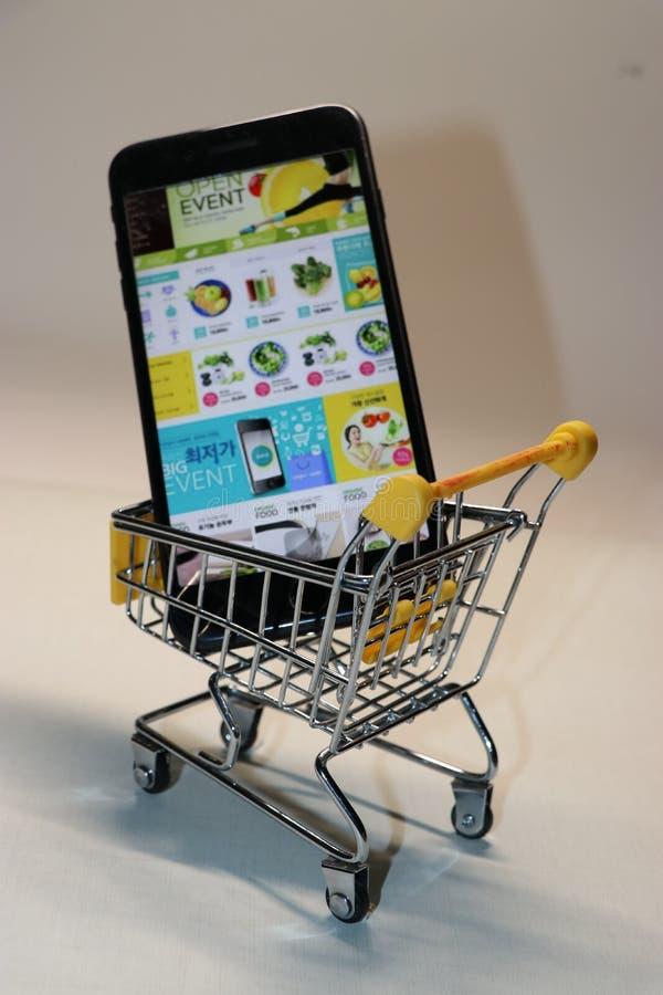 Der Handy ist in einem Warenkorb lizenzfreie stockfotos