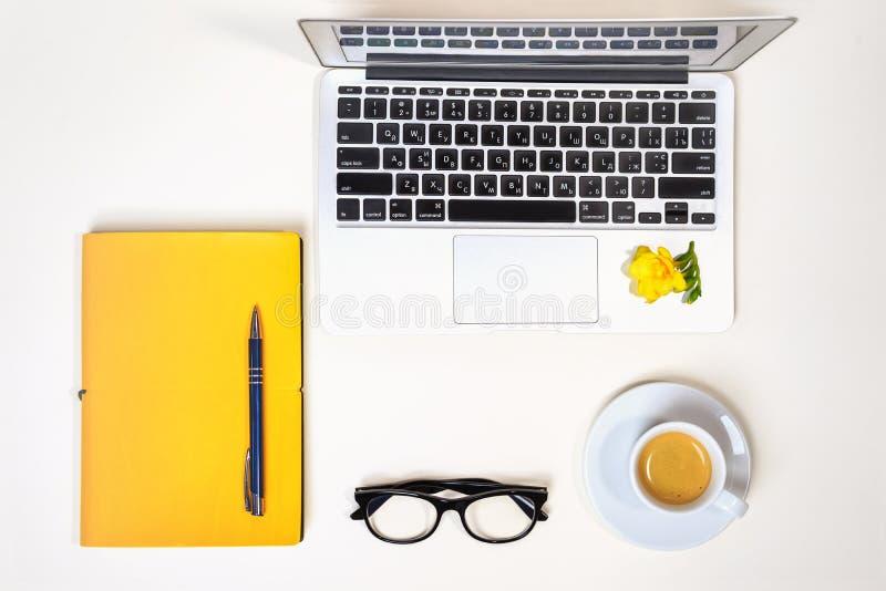 Der Hauptschreibtisch der Frauen Arbeitsplatz mit dem Laptop, Computer, gelbem Notizbuch, Modegläsern, Tasse Kaffee und Blume an  lizenzfreie stockfotos