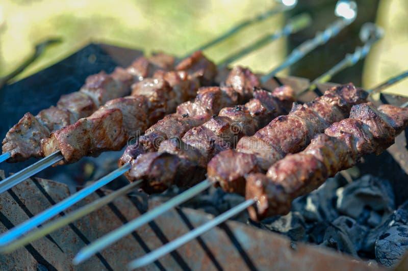 Der heiße Kebab, der auf Aufsteckspindeln festgesteckt wird, liegt auf dem Grill lizenzfreies stockbild