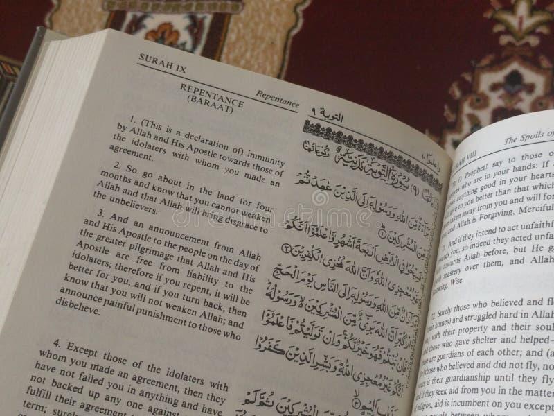 Der heilige Quran in englischem und in arabischem auf einer schönes Ost-Muster angeredeten Wolldecke stockbild