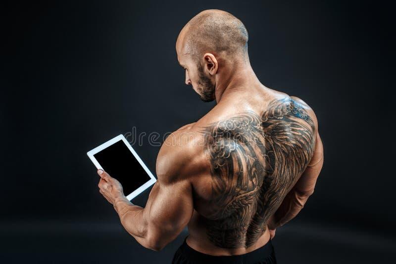 Der hemdlose kahle tatooed Mann, der Tablette verwendet, stehen zurück lizenzfreie stockfotografie