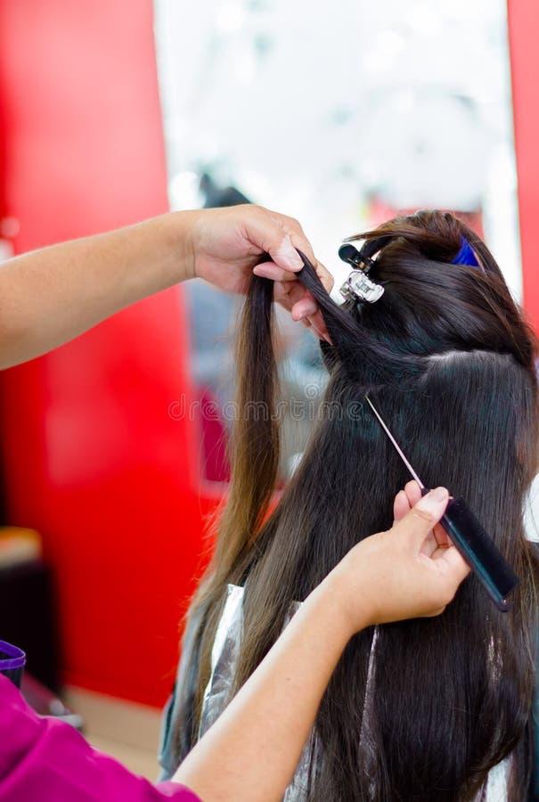 Der Herrenfriseur, der ein langes braunes Haar in den Schichten, ein Kamm vorbereitet, hilft ihr stockbilder