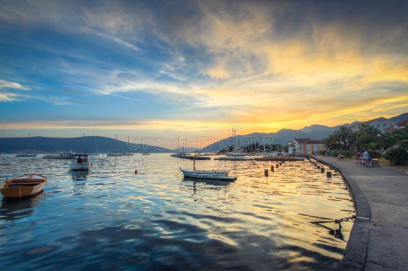 Der Himmel bei Sonnenuntergang reflektiert sich in der Perlmuttwasseroberfläche, auf der einsame Boote wandern stockbilder