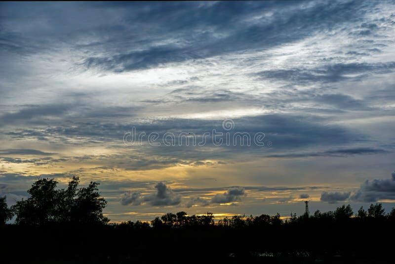 Der Himmel ist stumpf, bewölkt während des Abends nach Sonnenuntergang Die Front des Himmels ist ein Schattenbild des Baums Der H lizenzfreie stockfotos