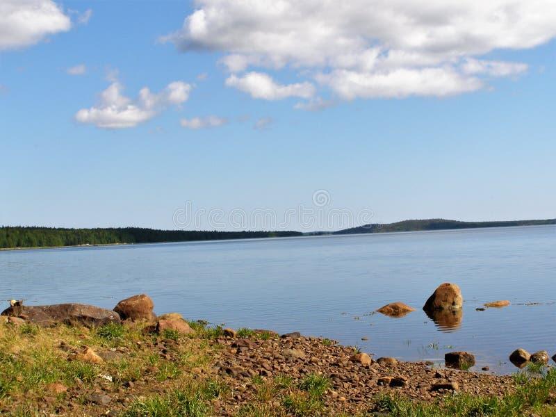 Der Himmel mit großen weißen Wolken über einem See mit einem steinigen Ufer lizenzfreie stockfotos