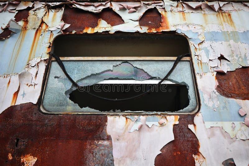 Der Hintergrund der alten Fenster des Zugs wird, gebrochenes, verrostetes, defektes Glas geschädigt lizenzfreie stockbilder