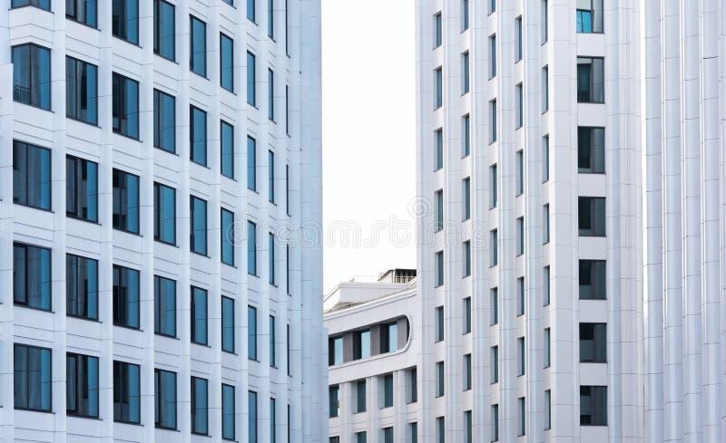 Der Hintergrund ist ein modernes Bürohaus Fragmente der weißen Fassaden des stilvollen Gebäudes stockfotografie