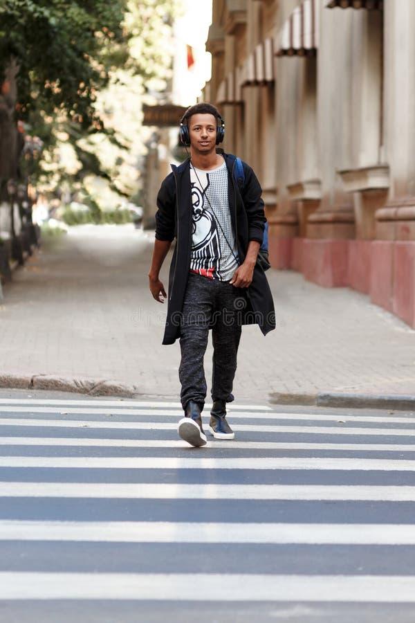 Der Hippie-Kerl, der mit atitudine auf dem h?renden Zebrastreifen eine Musik geht, geht, in der Tageszeit zu arbeiten, f?rdert zu lizenzfreies stockfoto