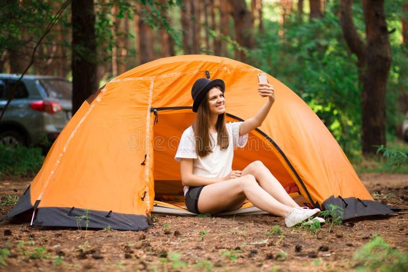 Der Hippie-Reisende der jungen Frau, der selfie Unterlassungssonnenuntergang tut, Touristen genießen Waldansicht lizenzfreies stockfoto