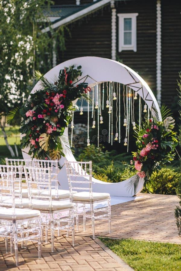Der Hochzeitsbogen auf dem Gebiet des Hotels in Form eines weißen Kreises verziert mit Blumen, Glühlampen und Kristall tran lizenzfreie stockbilder