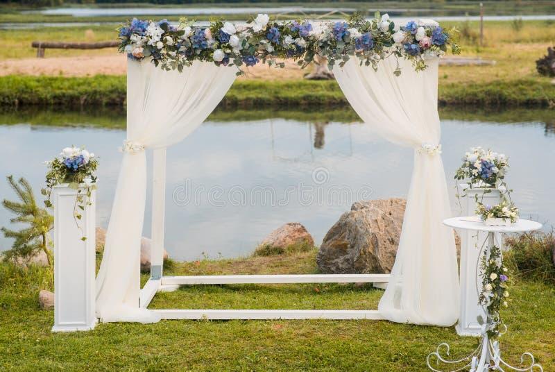 Der Hochzeitsbogen wird mit blauen Blumen und Seide des weißen Lichtes verziert Sommerhochzeitszeremonie lizenzfreie stockfotografie